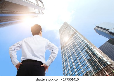 happy successful business man outdoors Next to Office Buildings with cityscape and sky, asian