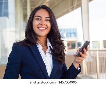 Happy successful business professional using cellphone outside. Beautiful young Latin woman in office suit holding smartphone and smiling at camera. Mobile internet concept