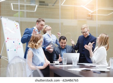 Happy successful business team giving a high fives gesture as they laugh and cheer their success. Signing an important contract, start up concept