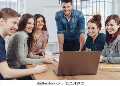 Happy successful business team looking at a laptop computer as they group around an office table smiling
