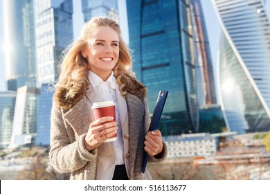 Happy successful business woman holding coffee and folder with documents