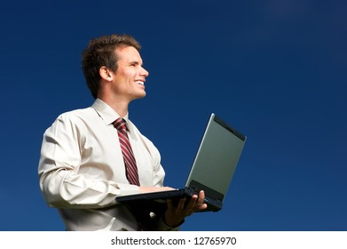 Happy successful  businessman with laptop   under blue sky.
