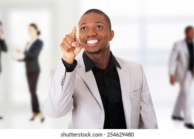 Happy successful businessman pointing on copy space.