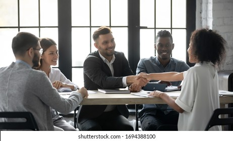 Happy successful businessman in suit shaking hand of african american businesswoman at company meeting. Diverse team fasten deal at hire. Leader in suit with assistant congratulates clients.