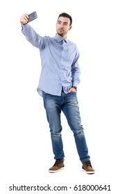 Happy successful businessman taking selfie looking at smart phone. Full body length portrait isolated over white background.
