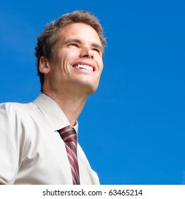 Happy successful  businessman  under blue sky. Portrait