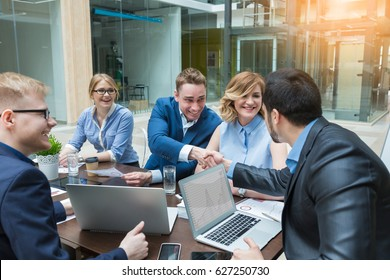 Happy successful Businesspeople shaking hands in board room