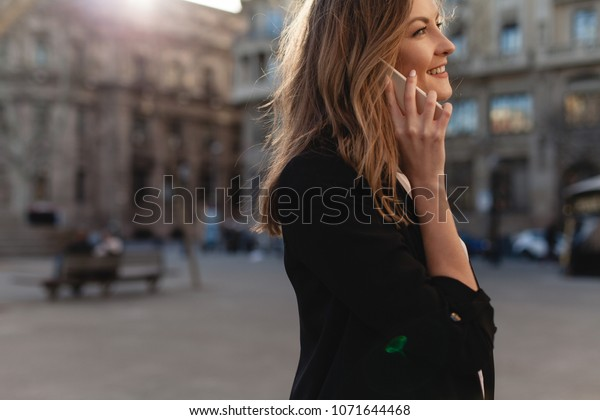 Happy successful businesswoman calling with cell telephone outside, smiling female entrepreneur managing business talking via mobile phone and walking on the city street,  making phone call after job
