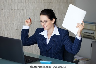 Happy successful businesswoman holding white paper at glass desk in office, teeth smile