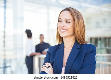 Happy successful businesswoman posing in office interior. Middle aged business woman standing for camera with arms folded, looking away and smiling. Business portrait concept