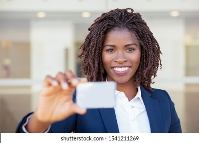 Happy successful businesswoman showing badge. Young African American business woman holding blank card, looking at camera, smiling. Introduction concept
