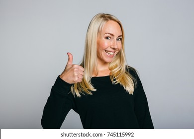 Happy successful confident woman in black t-shirt showing thumbs up . Handsome young woman gesturing and keeping mouth open while standing against grey background