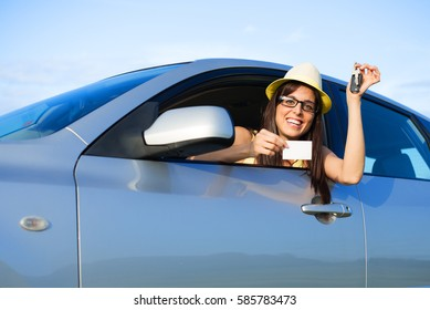 Happy successful female driver holding car keys and blank driving license.