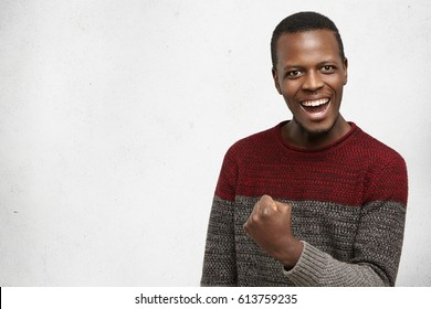 Happy successful lucky young dark-skinned man in warm sweater smiling joyfully, cheering, feeling excited about winning lottery, gesturing with hand, saying: Yes, I made it. Success, luck and victory