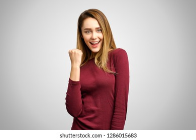 Happy successful lucky young woman smiling joyfully, cheering, feeling excited about winning lottery, gesturing with hand, saying: Yes, I made it. Success, luck and victory.