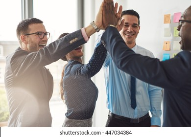 Happy successful multiracial business team giving a high fives gesture as they laugh and cheer their success