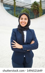 Happy successful Muslim businesswoman posing outside. Beautiful young business woman in black hijab and office suit standing for camera with arms folded and smiling. Muslim business lady concept