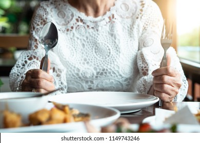 Happy successful old aging women facing midlife crisis empty plate eating disorder anorexia food boring health issue. Senior female sitting on table alone stop eat weight lose, diet, diabetes illness.