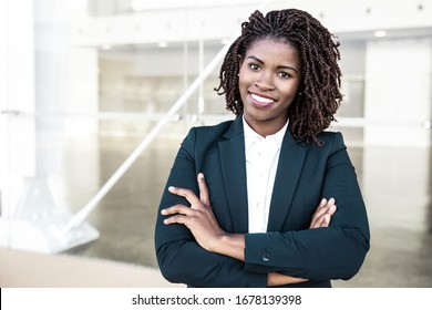 Happy successful professional posing near office building. Young African American business woman with arms folded standing outside, looking at camera, smiling. Female business leader concept