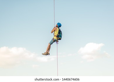 Happy successful rock climber hanging on rope above the sky