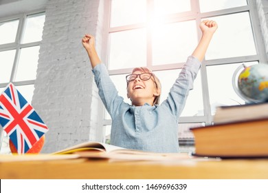 Happy successful schoolboy raises hands up in wide classroom, successful learning english language