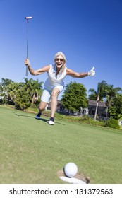 Happy successful senior woman playing golf putting a golf ball into a hole on a green and celebrating her success