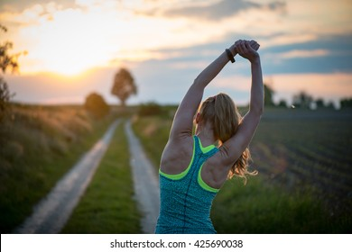 Happy successful sportswoman raising arms to the sky on golden back lighting sunset summer. Fitness athlete with arms up celebrating goals after sport exercising and working out outdoors.