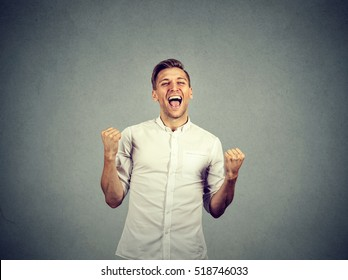 Happy successful student, business man winning, fists pumped celebrating success isolated grey wall background. Positive human emotion facial expression. Life perception, achievement