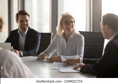 Happy successful well-dressed company members headed by aged woman in eyeglasses gathered together in boardroom at briefing. Business partners solve current matters negotiating sitting at office desk