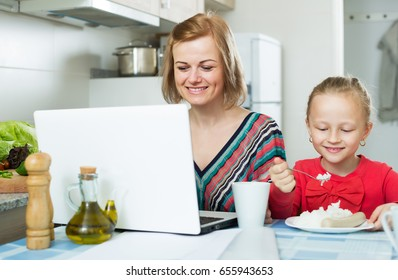 Happy successful woman with kid working from home using laptop