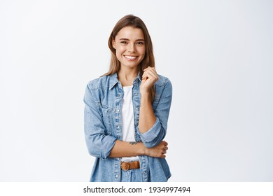 Happy successful woman standing in casual outfit, smiling pleased at camera and looking confident, standing against white background