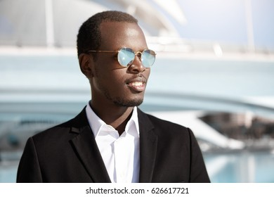 Happy successful young black employee in stylish formal wear and sunglasses looking cheerful, rejoicing at his career goals after having been promoted to upper post. People, lifestyle and business