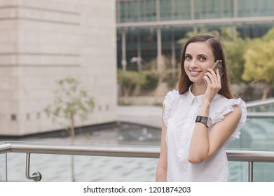 Happy and successful young business woman talking via mobile phone. European female calling via smartphone with positive face expression. Business situation