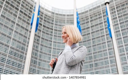 Happy successful young business womandressed in casual style, talking on the phone on the background of a modern building with EU flags. Business woman caucasian near the building of the European