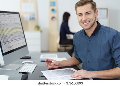 Happy successful young businessman at his desk in the office working on a report looking at the camera with a warm smile