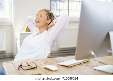 Happy successful young businesswoman relaxing in her chair in the office with closed eyes and a satisfied smile