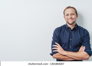 Happy successful young man with a pleased smile standing with folded arms and a satisfied expression over white with copy space