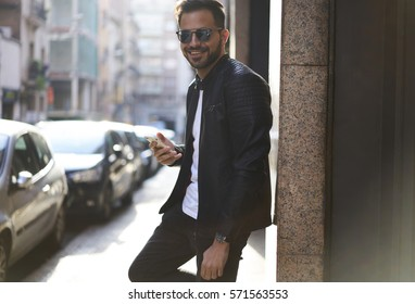 Happy and successful young man standing in city with smartphone in hands, smiling hipster guy using fast 4G network connection on his cellular device. Copy space for promotional content or advertising