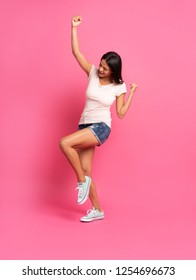 Happy successful young woman with raised hands shouting and celebrating success over pink background