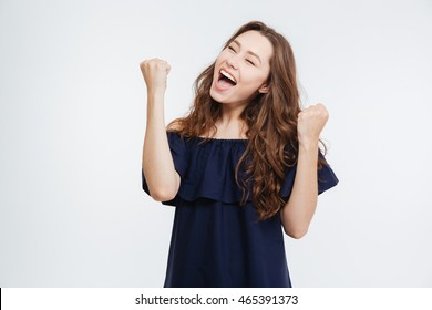 Happy successful young woman with raised hands shouting and celebrating success over white background