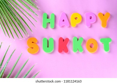 Happy Sukkot hebrew holiday greeting card with green palm leaf and greeting text happy sukkot on pink background. Colorful letters.