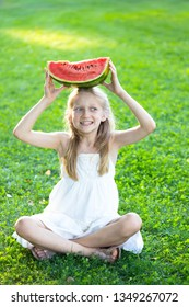 happy summer - beautiful blond little girl eating watermelon on a green lawn