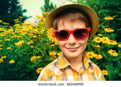 Happy summer boy in sunglasses and straw hat at a park on a sunny day. Happy childhood. Holidays.
