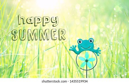 Happy Summer. cute funny scene with frog toy in grass in sunny meadow. concept of summer season, children's vacation. copy space
