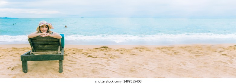 Happy summer holiday vacation on the seaside beach, Traveller tourist woman with hat enjoying and relaxing on the chair at Pataya beach, Thailand, panorama shot for banner.