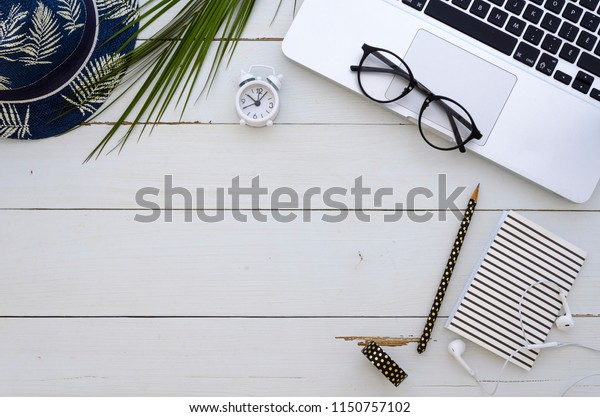 Happy summer time. Freelancer - travel blogger workspace. Computer and photo camera top view mock up. Flat lay