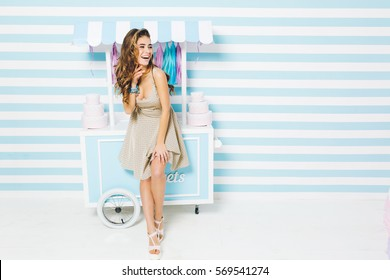 Happy summer time of pretty fashionable model in dress having fun on striped background. Sweet dessert truck, cakes, laughing, expressing true positive emotions. Place for text