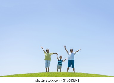 Happy summer vacation for kids on green meadow near sea