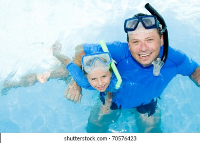 Happy summer vacation - little girl with father snorkeling in blue water