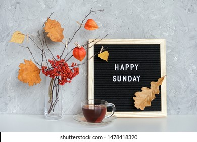 Happy Sunday text on black letter board and bouquet of branches with yellow leaves on clothespins in vase and cup of tea on table Template for postcard, greeting card Concept Hello autumn Sunday.